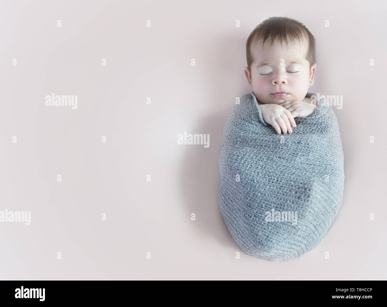 Newborn girl slepping wrapping in a gray blanket - Stock Image