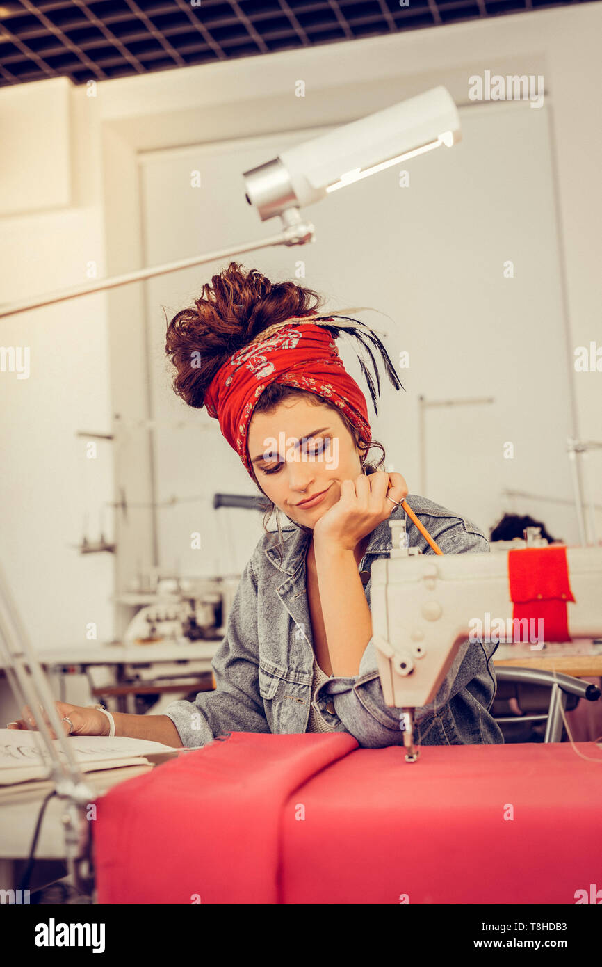 Designer looking at her scketches and thinking about improving them. - Stock Image