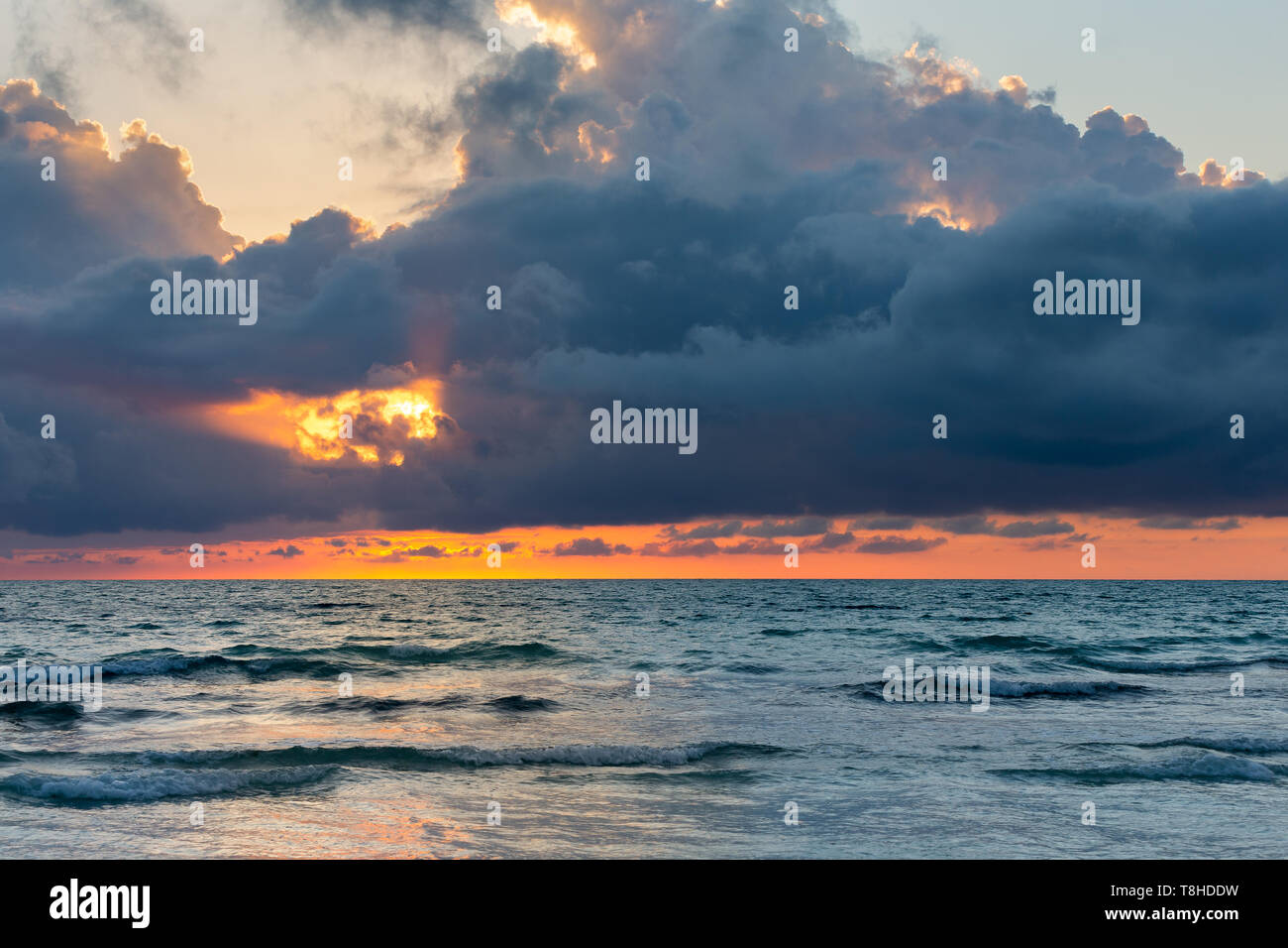 Ocean sunset or sunrise background with dramatic storm clouds and orange reflections on the water. - Stock Image