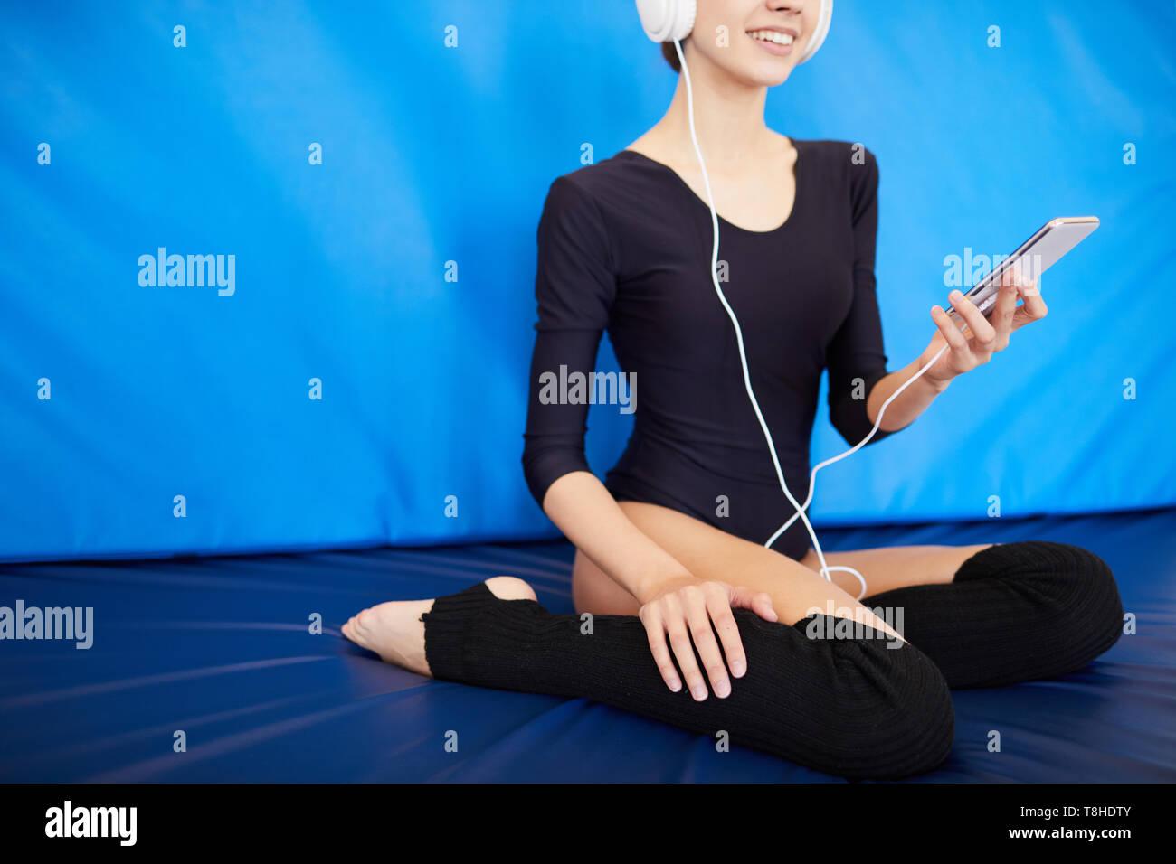 Positive gymnast listening to music in headphones - Stock Image