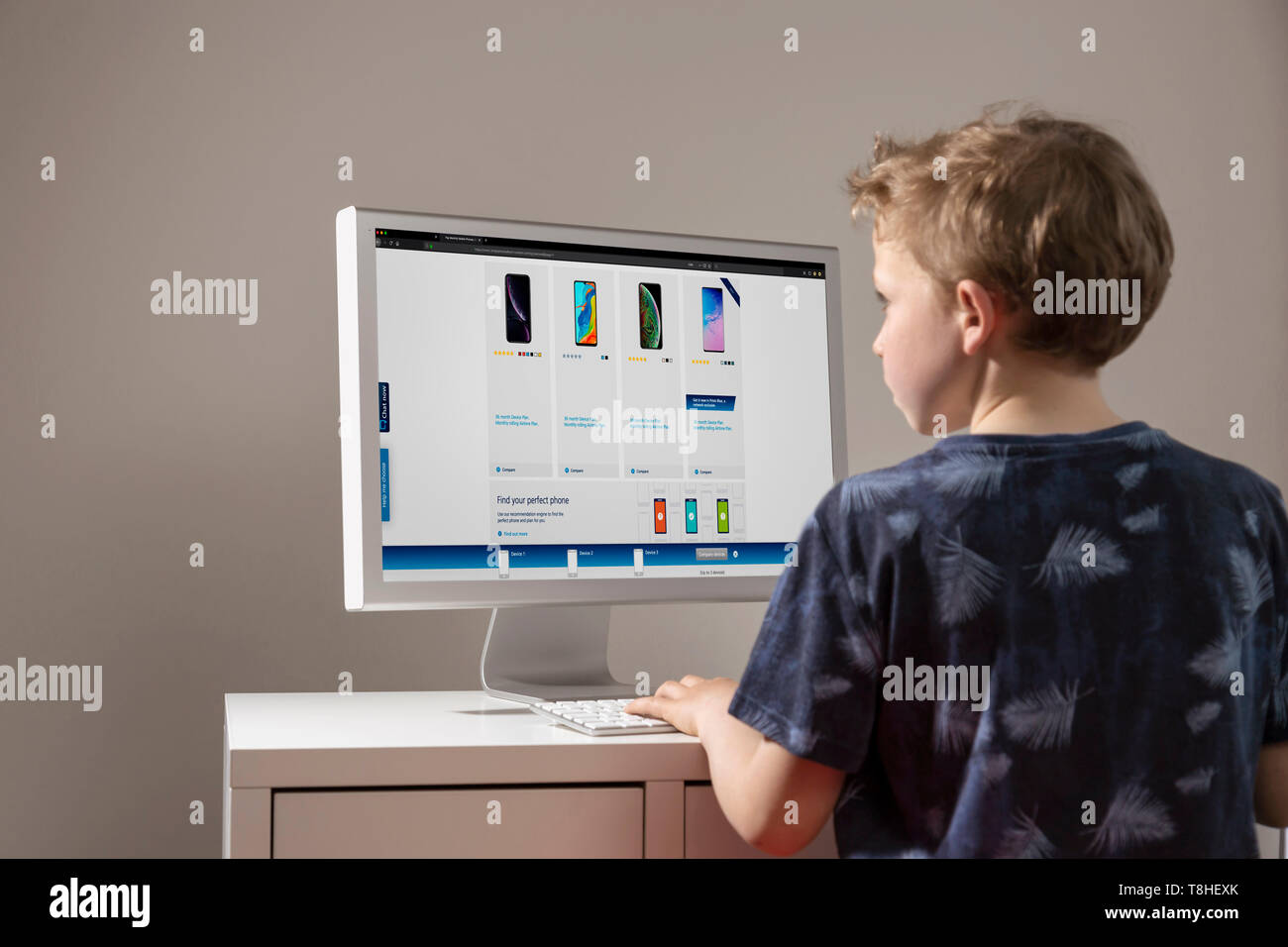 Boy looking at offers for mobile phones in the Internet - Stock Image