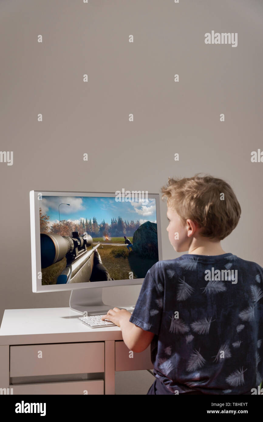 Boy, 8 years, playing a first-person shooter at the computer - Stock Image
