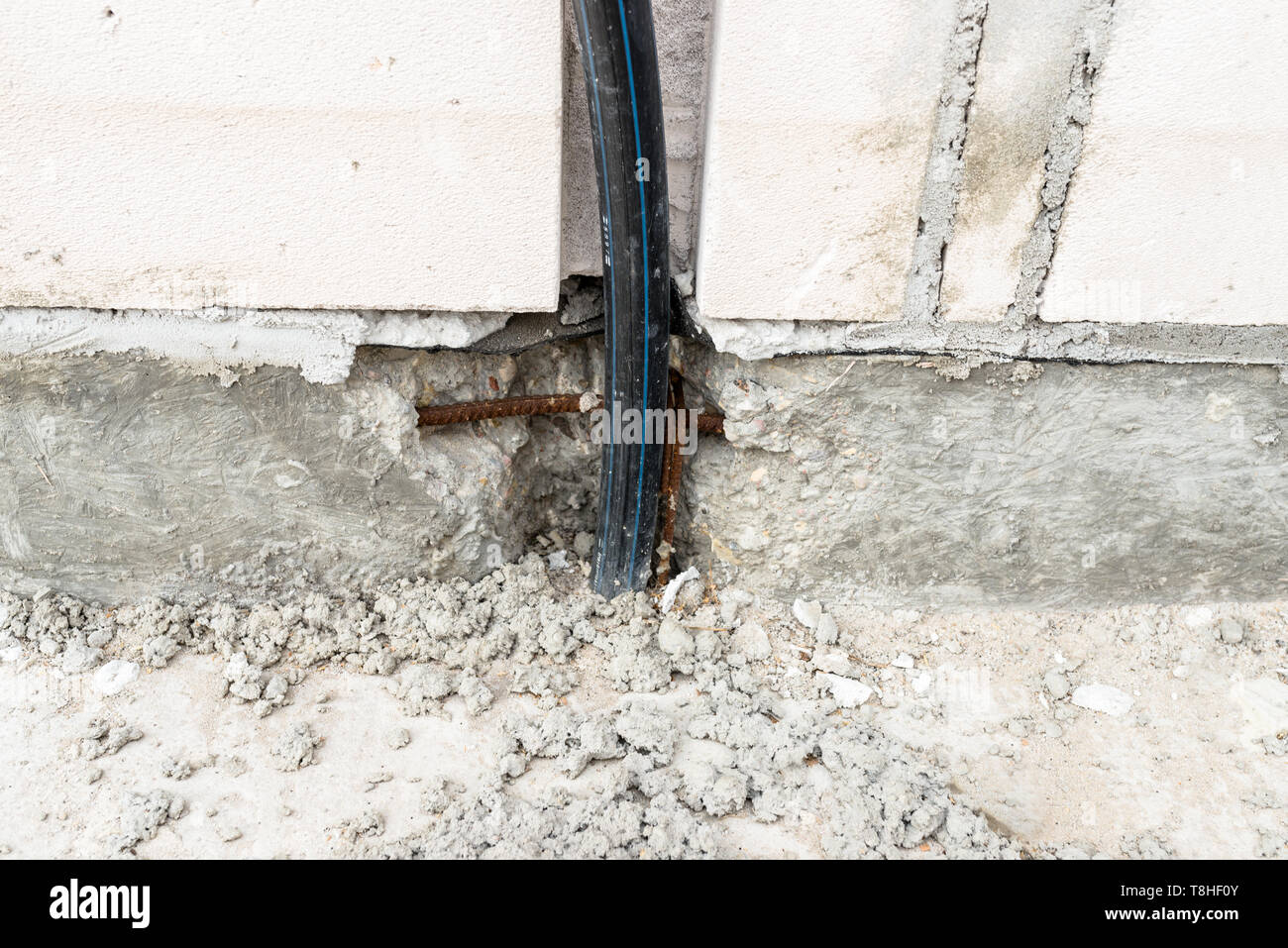 An electric high voltage cable protruding from the foundation of the house being built. - Stock Image