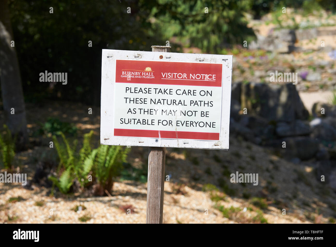 Warning notice about uneven pathways (Sidewalks) - Stock Image