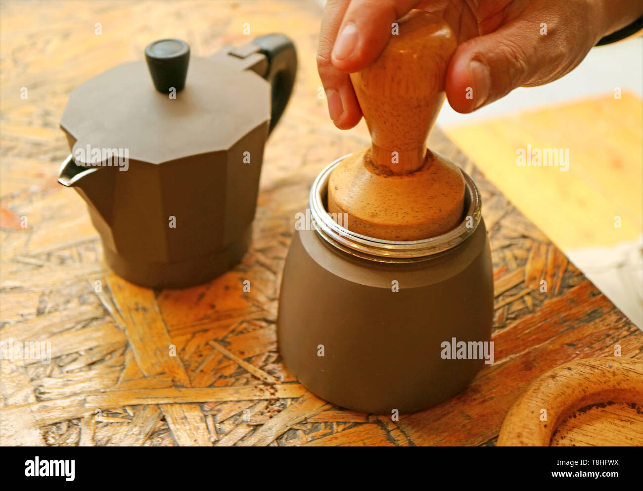 Hand Slightly Tapping Ground Coffee with Wooden Tamper for a Flat Surface before Brewing Aromatic Coffee - Stock Image