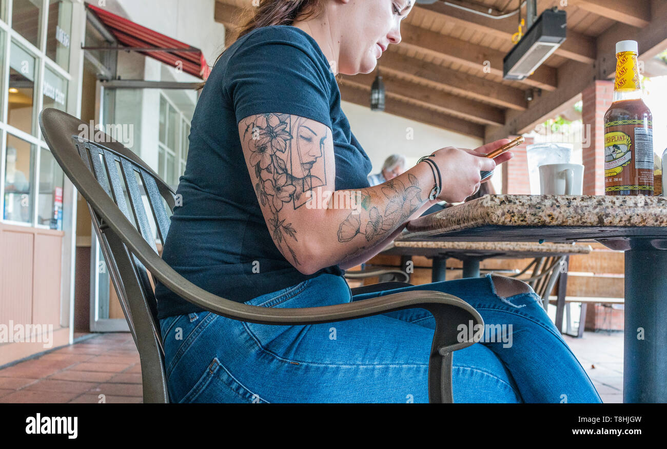 5edbf081f1a8c A young female adult with an arm tattoo of a female face while sitting at a