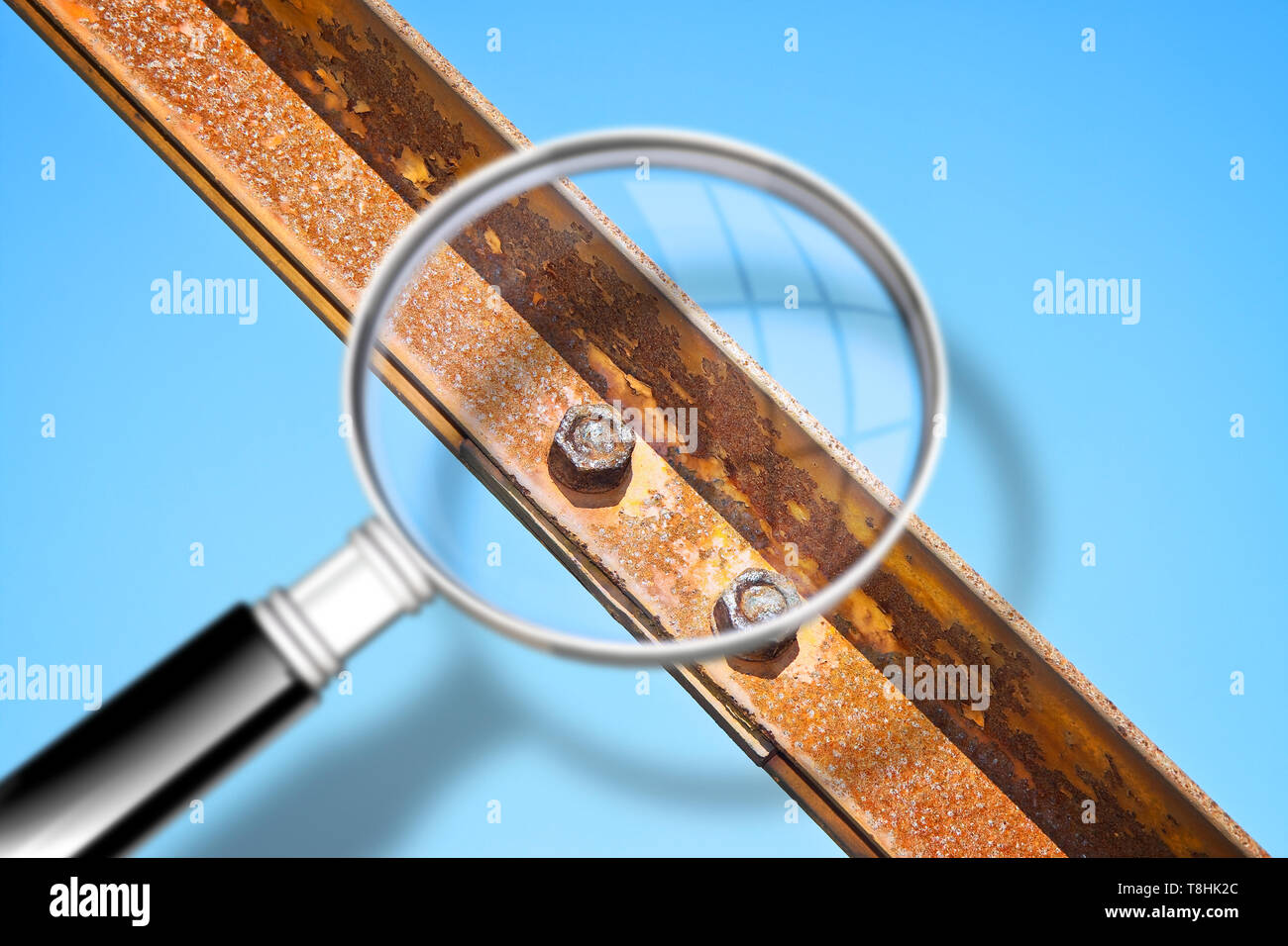 Old rusty iron structure with bolted metal profiles against a blue sky - Concept image seen through a magnifying glass - Stock Image