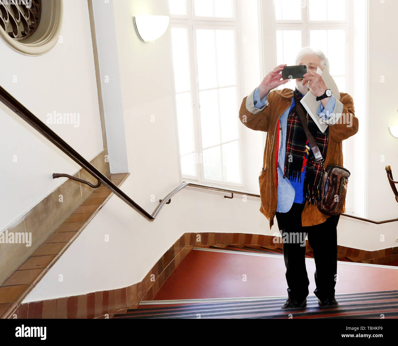 Duisburg, Germany. 13th May, 2019. The publicist Henryk M. Broder, accused of insulting the accused, films the people present with his smartphone before the trial begins. In September 2016, at the request of the weekly newspaper 'Junge Freiheit', Broder had said about the Islamic scholar Lamya Kaddor that she had 'a gossip on her hands'. Broder appealed against an order of punishment, which is why the trial is now at trial. Credit: Roland Weihrauch/dpa/Alamy Live News - Stock Image