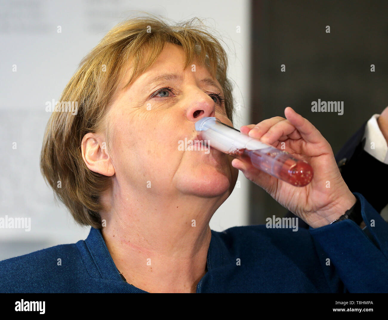 Wuppertal, Germany. 09th May, 2019. Chancellor Angela Merkel (CDU) drinks dry ice with syrup from a test tube at Wuppertal Junior University. The Wuppertal Junior University is a nationwide unique extracurricular educational and research institution for 4 to 20 year olds. Credit: Oliver Berg/dpa/Alamy Live News - Stock Image