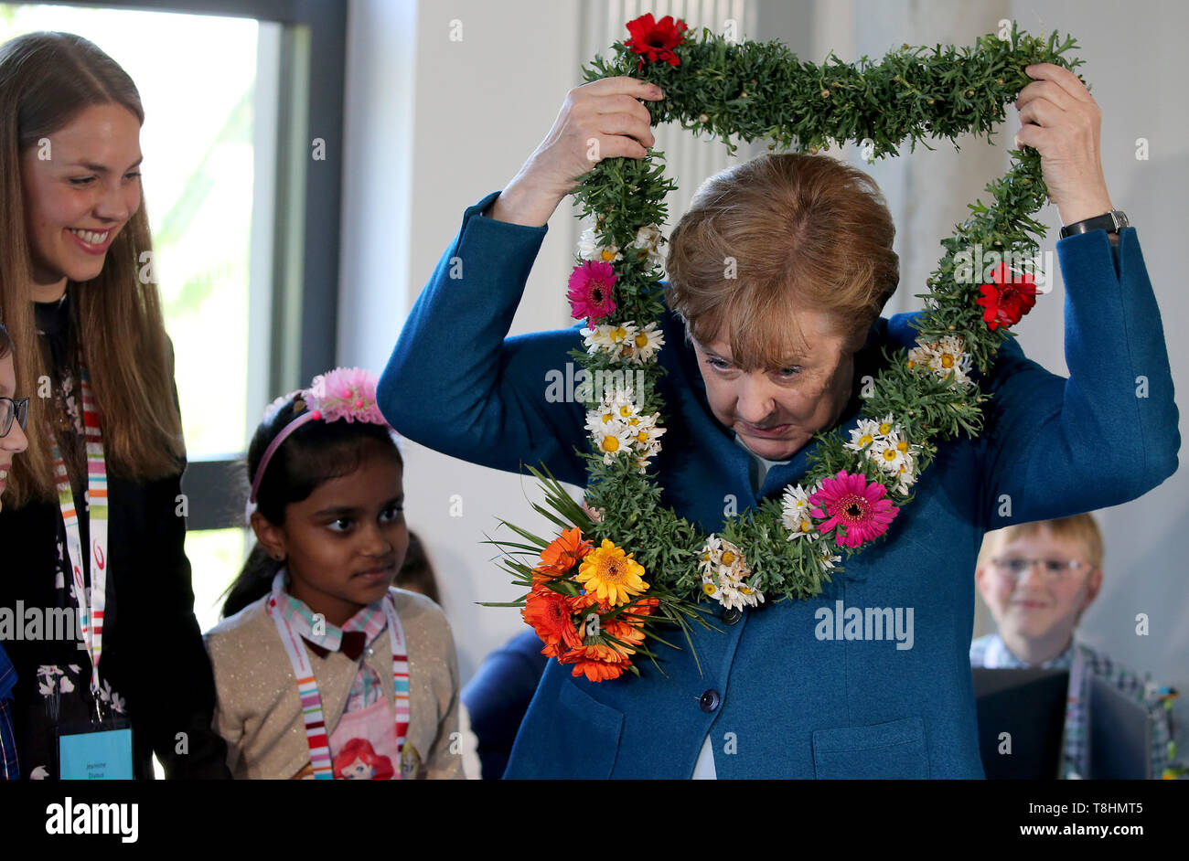 Wuppertal, Germany. 09th May, 2019. Federal Chancellor Angela Merkel (r, CDU) receives a wreath of flowers from the Sri Lankan student Sadurthika Mahenthdran (M) at the Junior University. The Wuppertal Junior University is a nationwide unique extracurricular educational and research institution for 4 to 20 year olds. Credit: Oliver Berg/dpa/Alamy Live News - Stock Image