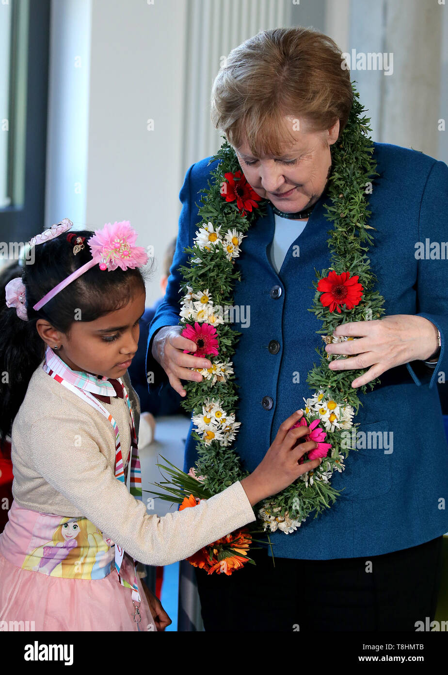 Wuppertal, Germany. 09th May, 2019. Federal Chancellor Angela Merkel (r, CDU) receives a wreath of flowers from the Sri Lankan student Sadurthika Mahenthdran (l) at the Junior University. The Wuppertal Junior University is a nationwide unique extracurricular educational and research institution for 4 to 20 year olds. Credit: Oliver Berg/dpa/Alamy Live News - Stock Image