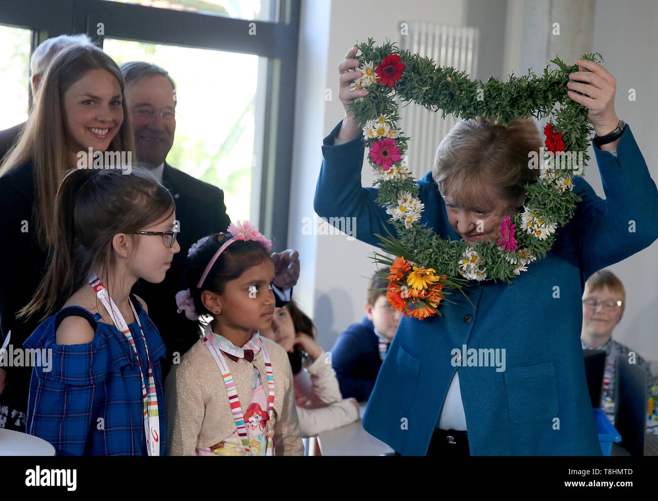 Wuppertal, Germany. 09th May, 2019. Federal Chancellor Angela Merkel (r, CDU) receives a wreath of flowers from the Sri Lankan student Sadurthika Mahenthdran (2nd from right) at the Junior University. The Wuppertal Junior University is a nationwide unique extracurricular educational and research institution for 4 to 20 year olds. Credit: Oliver Berg/dpa/Alamy Live News - Stock Image