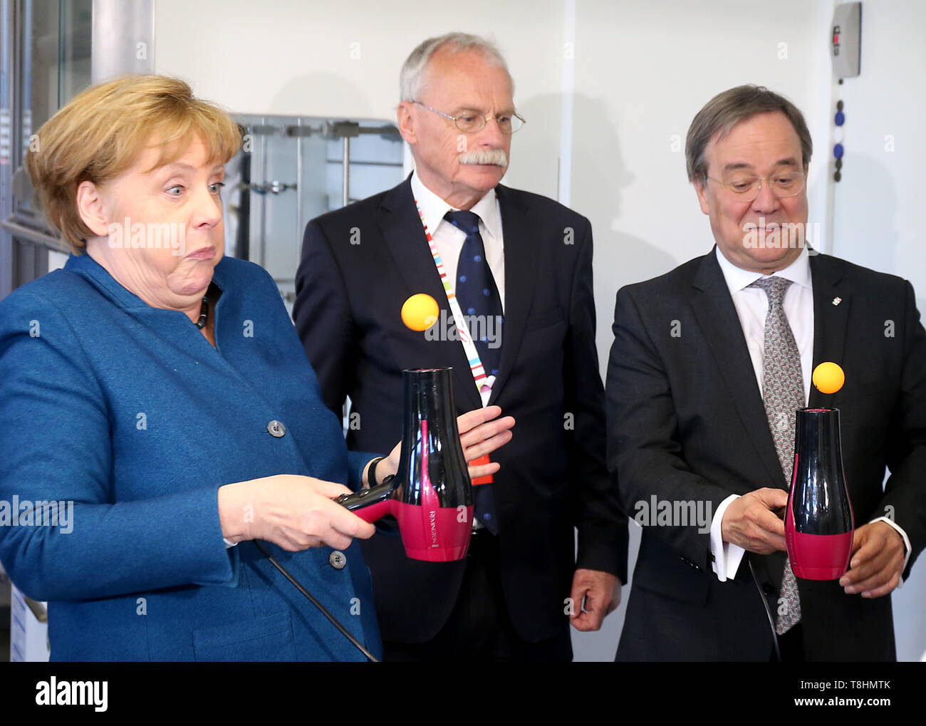 Wuppertal, Germany. 09th May, 2019. Federal Chancellor Angela Merkel (l, CDU), Armin Laschet, Prime Minister of North Rhine-Westphalia(r, CDU), and the founder of the Junior University Ernst-Andreas Ziegler (M) do an experiment on the Bernoulli effect and juggle a table tennis ball on a hairdryer. The Wuppertal Junior University is a nationwide unique extracurricular educational and research institution for 4 to 20 year olds. Credit: Oliver Berg/dpa/Alamy Live News - Stock Image