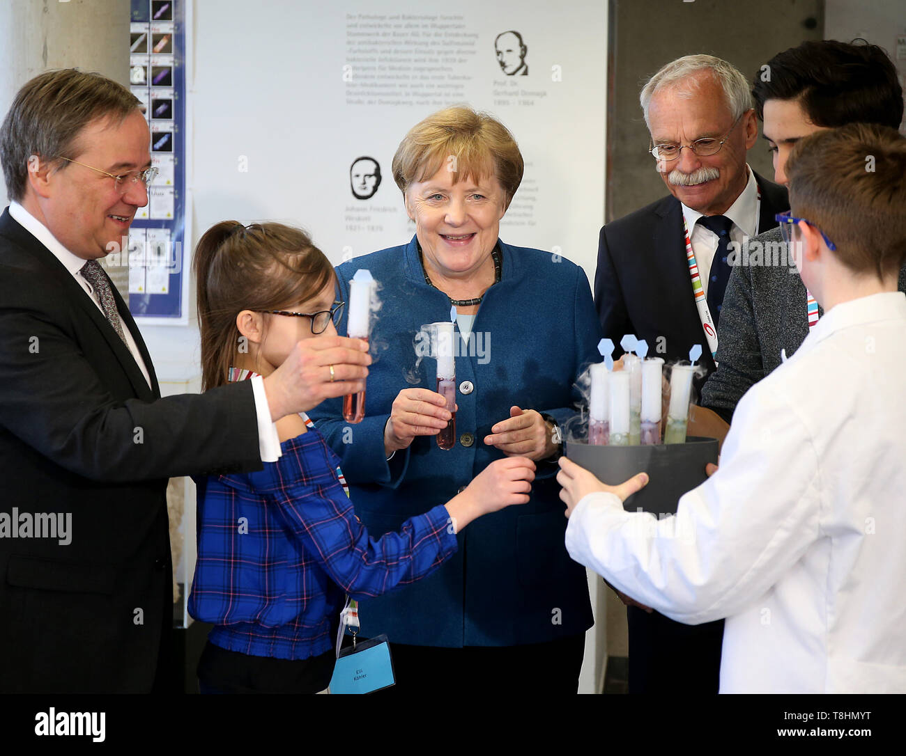 Wuppertal, Germany. 13th May, 2019. Federal Chancellor Angela Merkel (M, CDU), Armin Laschet, Prime Minister of North Rhine-Westphalia (l, CDU), and the founder of the Junior University Ernst-Andreas Ziegler (2nd from right) are presented with dry ice with syrup in a test tube by pupils. The Wuppertal Junior University is a nationwide unique extracurricular educational and research institution for 4 to 20 year olds. Credit: Oliver Berg/dpa/Alamy Live News - Stock Image