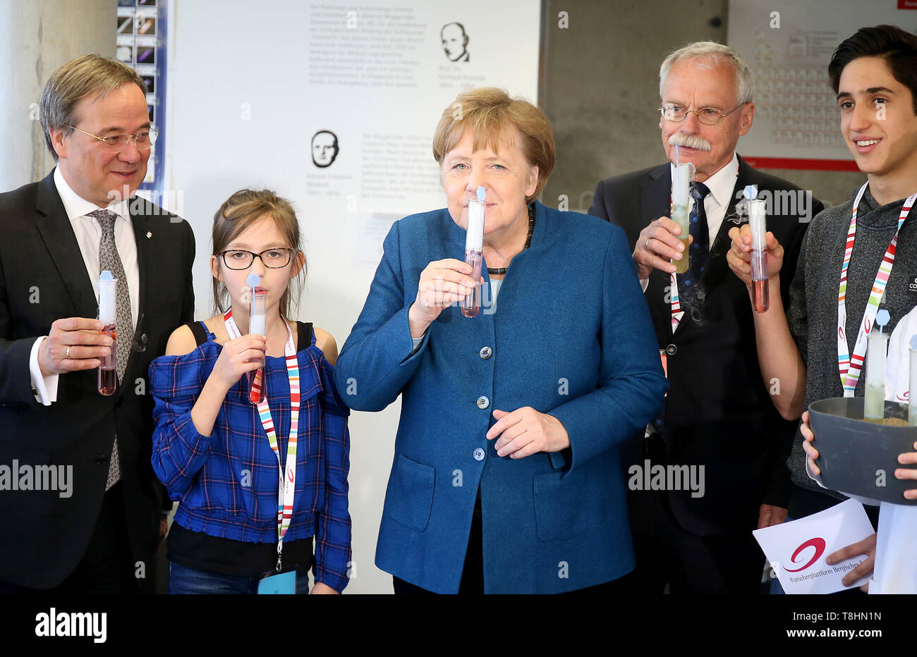 Wuppertal, Germany. 13th May, 2019. Federal Chancellor Angela Merkel (M, CDU), Armin Laschet, Prime Minister of North Rhine-Westphalia (l, CDU), and the founder of the Junior University Ernst-Andreas Ziegler (2nd from right) drink with the students Ellis (2nd from left) and Vito (r) dry ice with syrup from a test tube. The Wuppertal Junior University is a nationwide unique extracurricular educational and research institution for 4 to 20 year olds. Credit: Oliver Berg/dpa/Alamy Live News - Stock Image