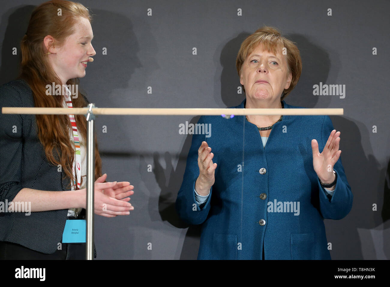 Wuppertal, Germany. 13th May, 2019. Federal Chancellor Angela Merkel (r, CDU) is pursuing a pendulum experiment at the Junior University alongside student Antonia Westphal. The Wuppertal Junior University is a nationwide unique extracurricular educational and research institution for 4 to 20 year olds. Credit: Oliver Berg/dpa/Alamy Live News - Stock Image
