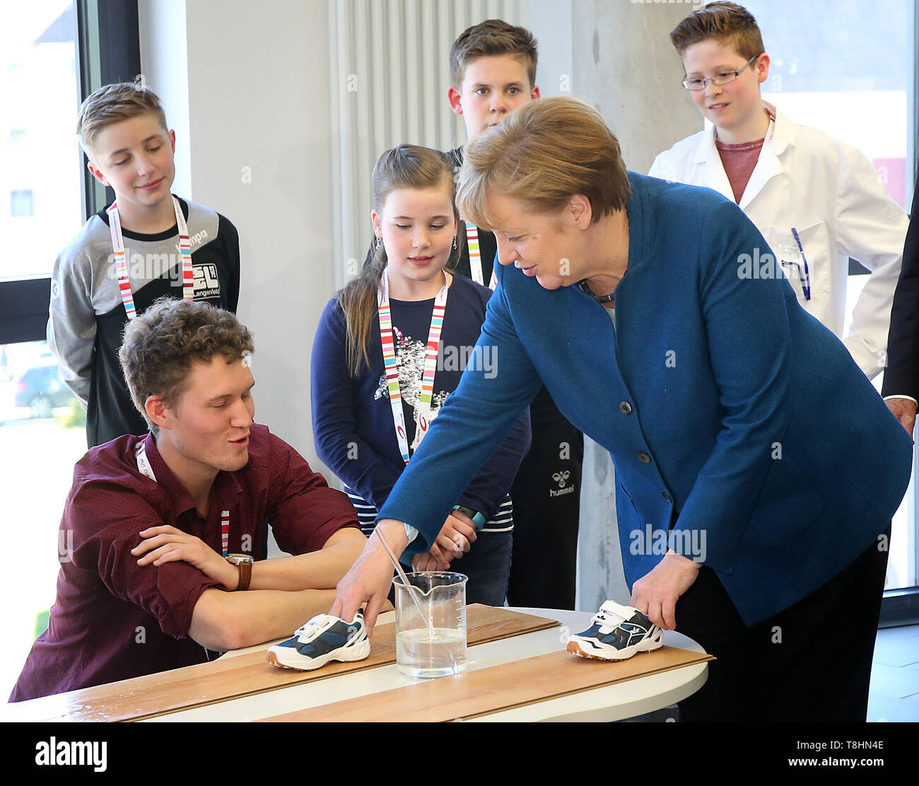 Wuppertal, Germany. 13th May, 2019. Chancellor Angela Merkel (r, CDU) conducts an experiment with the students at the Junior University on the slip resistance of surfaces. The Wuppertal Junior University is a nationwide unique extracurricular educational and research institution for 4 to 20 year olds. Credit: Oliver Berg/dpa/Alamy Live News - Stock Image