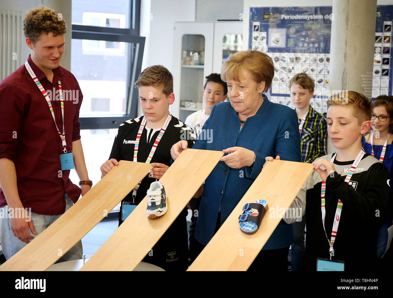 Wuppertal, Germany. 13th May, 2019. Chancellor Angela Merkel (M, CDU) conducts an experiment with the students at the Junior University on the slip resistance of surfaces. The Wuppertal Junior University is a nationwide unique extracurricular educational and research institution for 4 to 20 year olds. Credit: Oliver Berg/dpa/Alamy Live News - Stock Image