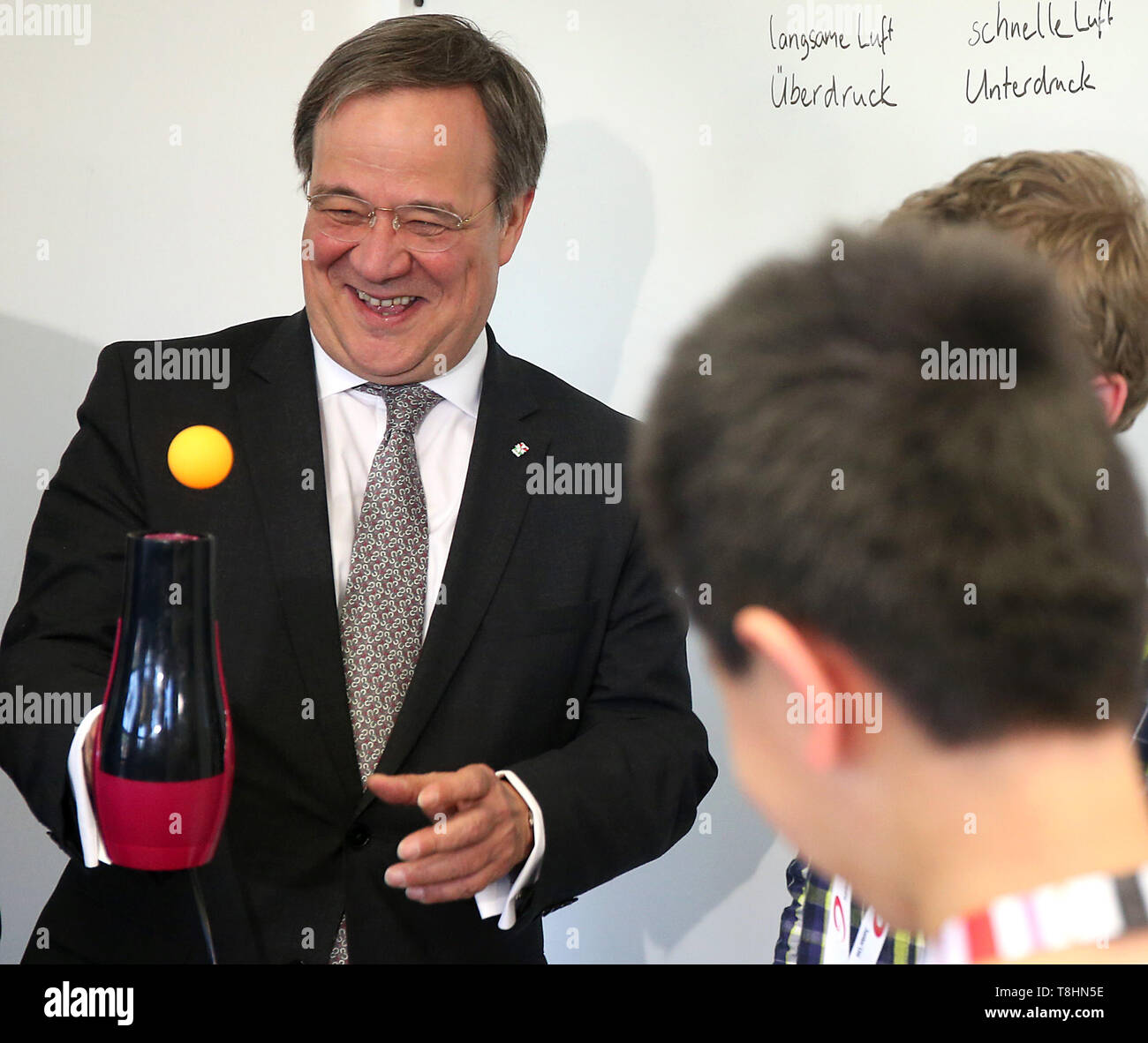 Wuppertal, Germany. 13th May, 2019. Armin Laschet, Prime Minister of North Rhine-Westphalia (r, CDU) is doing an experiment on the Bernoulli effect at the Junior University and juggling a table tennis ball on a hairdryer. The Wuppertal Junior University is a nationwide unique extracurricular educational and research institution for 4 to 20 year olds. Credit: Oliver Berg/dpa/Alamy Live News - Stock Image