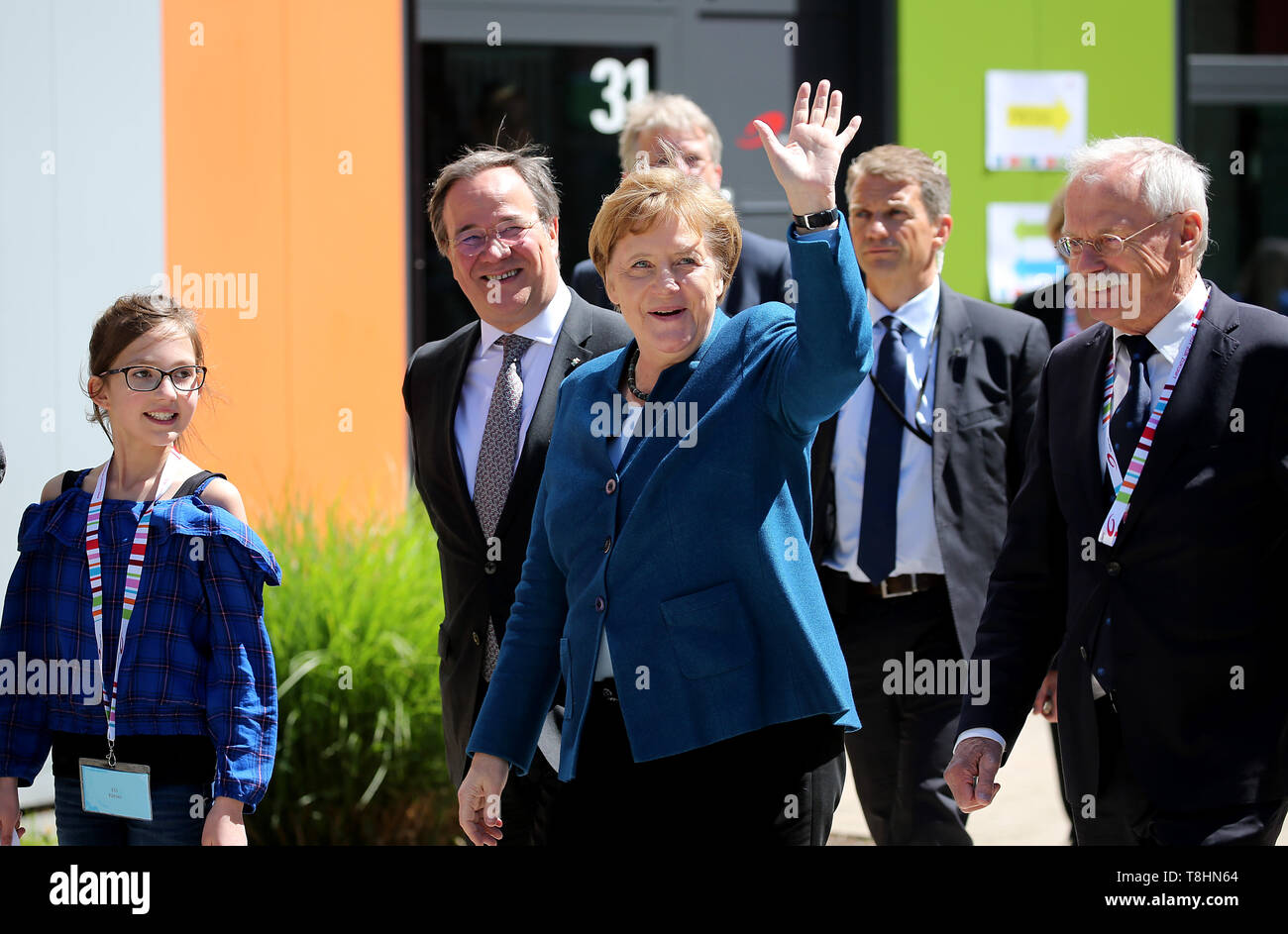 Wuppertal, Germany. 13th May, 2019. Federal Chancellor Angela Merkel (M, CDU), Armin Laschet, Prime Minister of North Rhine-Westphalia (2nd from left, CDU), and the founder of the Junior University Ernst-Andreas Ziegler (r) come to the Junior University with pupil Ellis (l). The Wuppertal Junior University is a nationwide unique extracurricular educational and research institution for 4 to 20 year olds. Credit: Oliver Berg/dpa/Alamy Live News - Stock Image