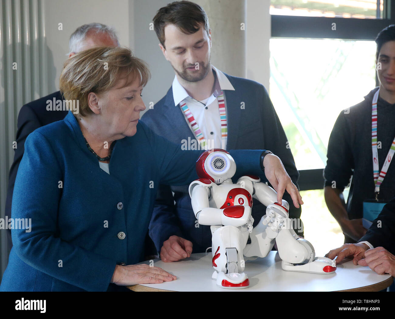 Wuppertal, Germany. 13th May, 2019. Chancellor Angela Merkel (l, CDU) plays with a robot at the Junior University. The Wuppertal Junior University is a nationwide unique extracurricular educational and research institution for 4 to 20 year olds. Credit: Oliver Berg/dpa/Alamy Live News - Stock Image