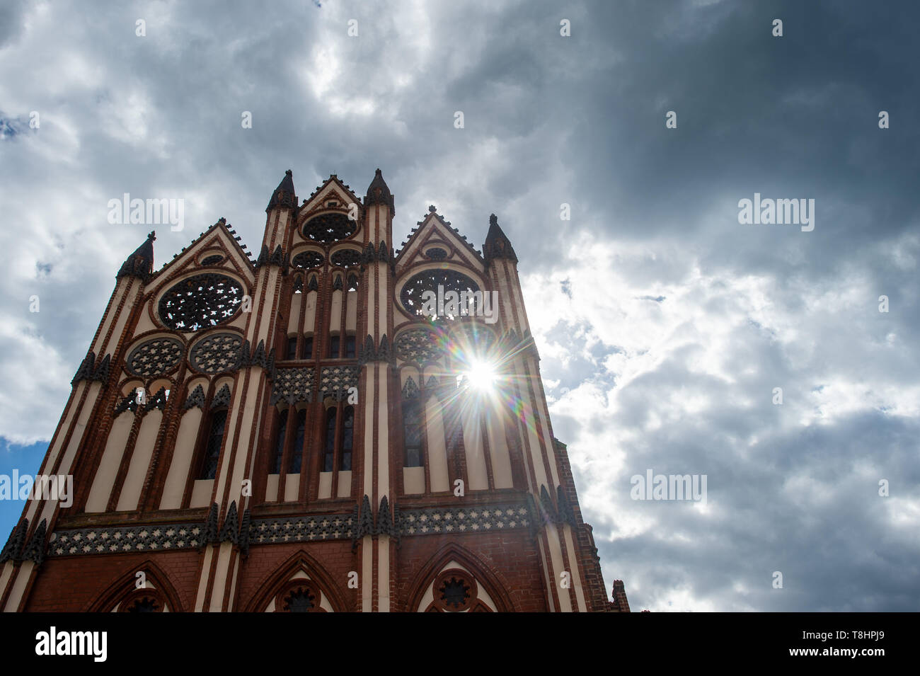 13 May 2019, Saxony-Anhalt, Tangermünde: The sun shines through a window in the façade of the town hall, while dark clouds pass over it. In the coming days the Altmark will remain changeable. Photo: Klaus-Dietmar Gabbert/dpa-Zentralbild/ZB - Stock Image