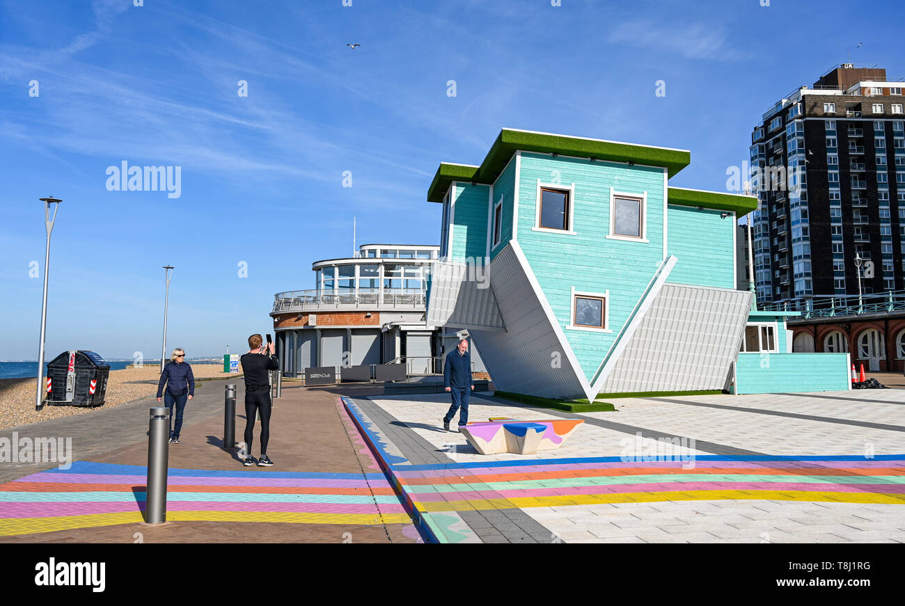Brighton, UK. 14th May, 2019. Early morning walkers take a look at Brighton's newest tourist attraction the Upside Down House on the seafront near the West Pier on a beautiful sunny morning with temperatures reaching into the twenties in some parts of Britain today. The Upside Down House is due to open to the public this coming weekend . Credit: Simon Dack/Alamy Live News Stock Photo