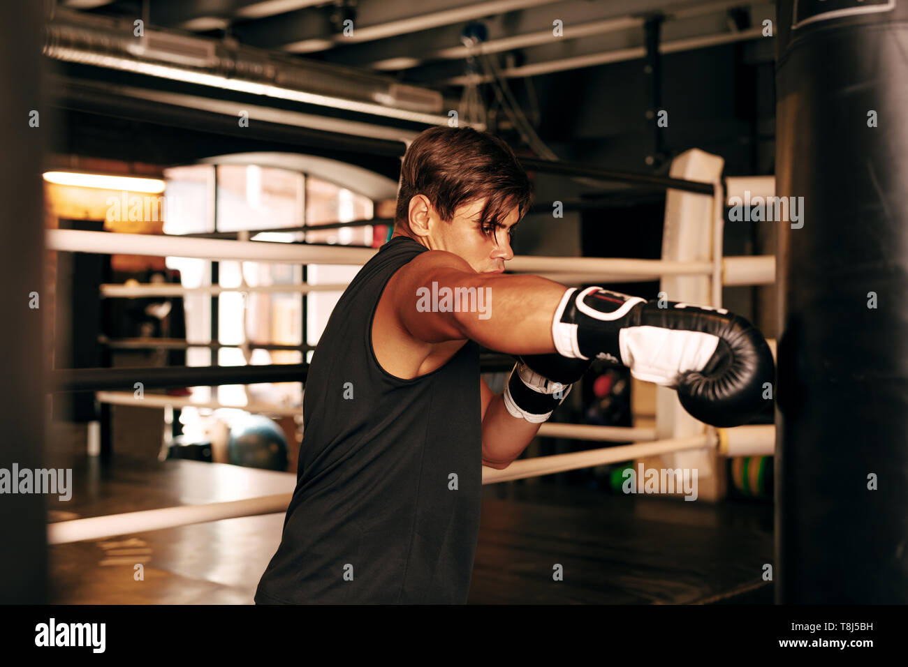 Muscular athlete working out in a gym on a leather punching bag - Stock Image