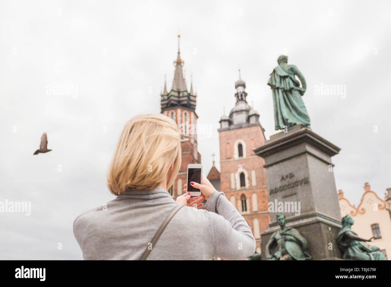 Young beautiful woman on the background of the St. Mary's Church in Krakow - Stock Image