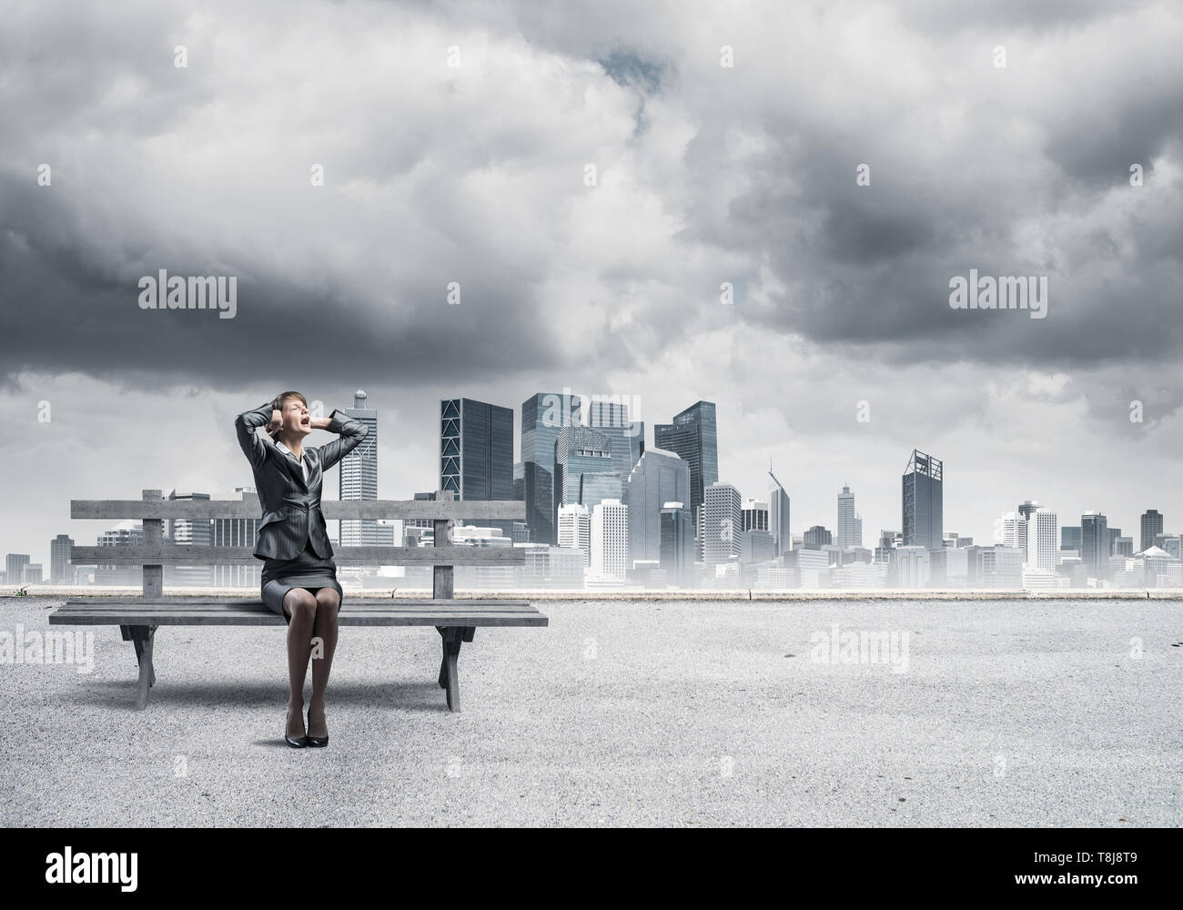 Stressful woman sitting on wooden bench - Stock Image
