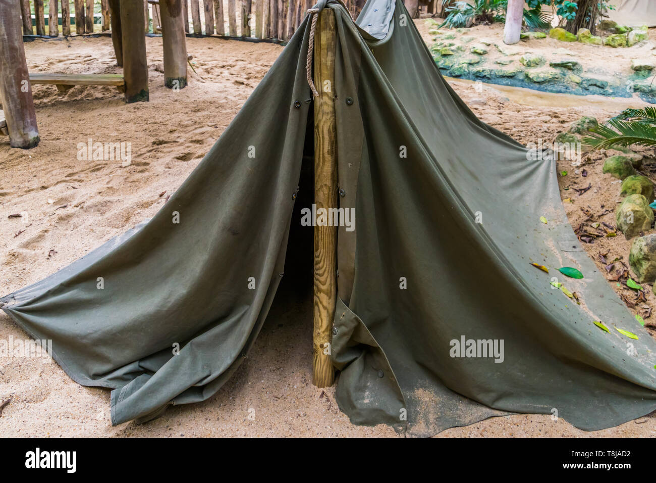 simple camping tent made out of a wooden pole and a canvas, basic survival equipment - Stock Image