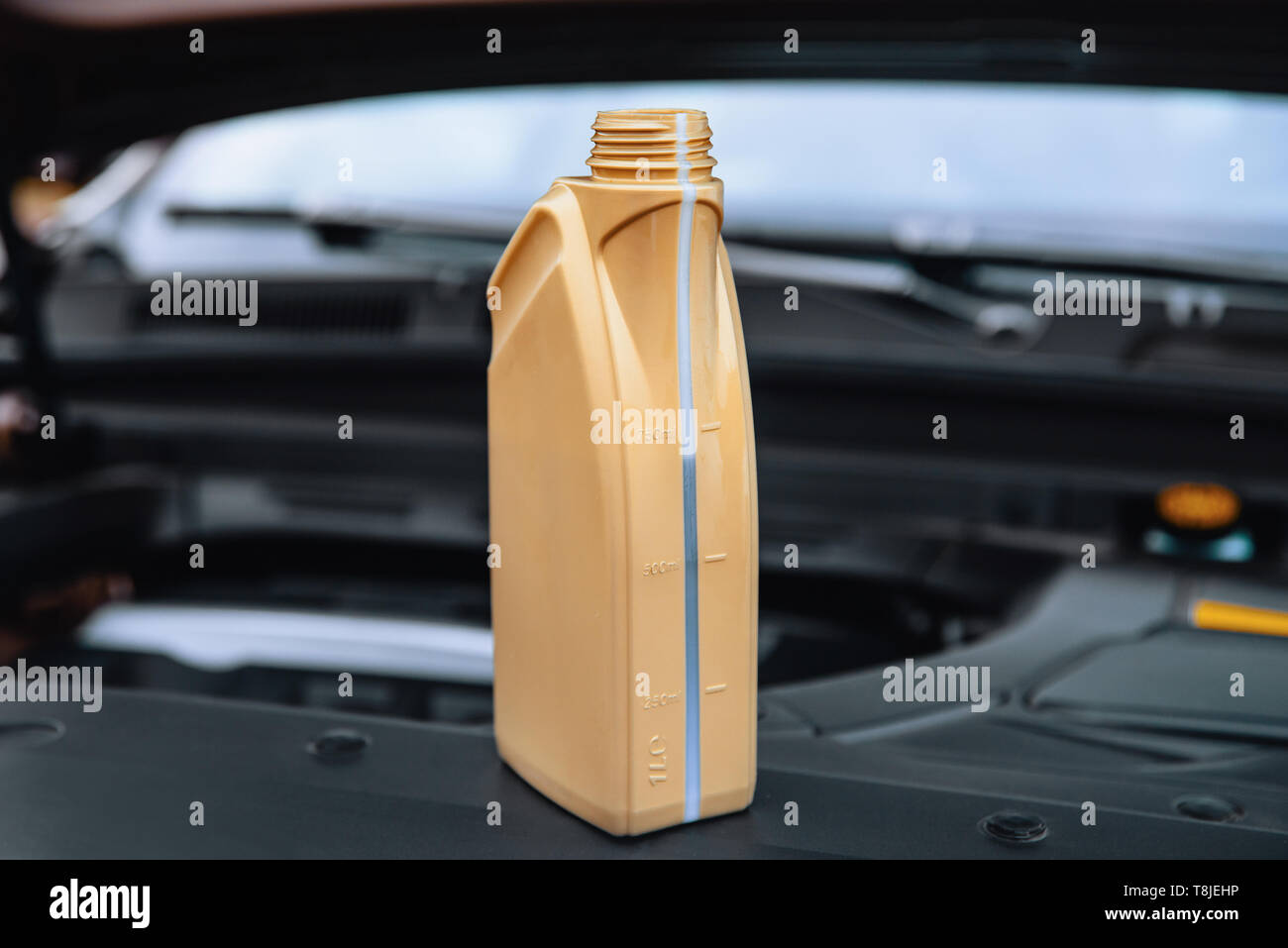 Capacity with engine oil near the car engine - Stock Image
