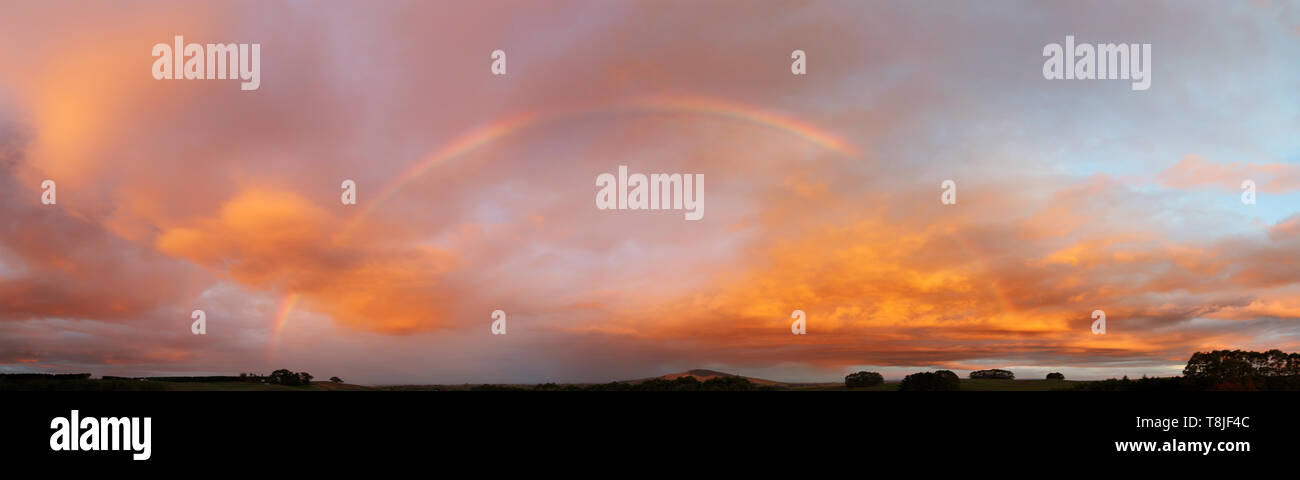 Rainbow in sunset sky over New Zealand landscape - Stock Image
