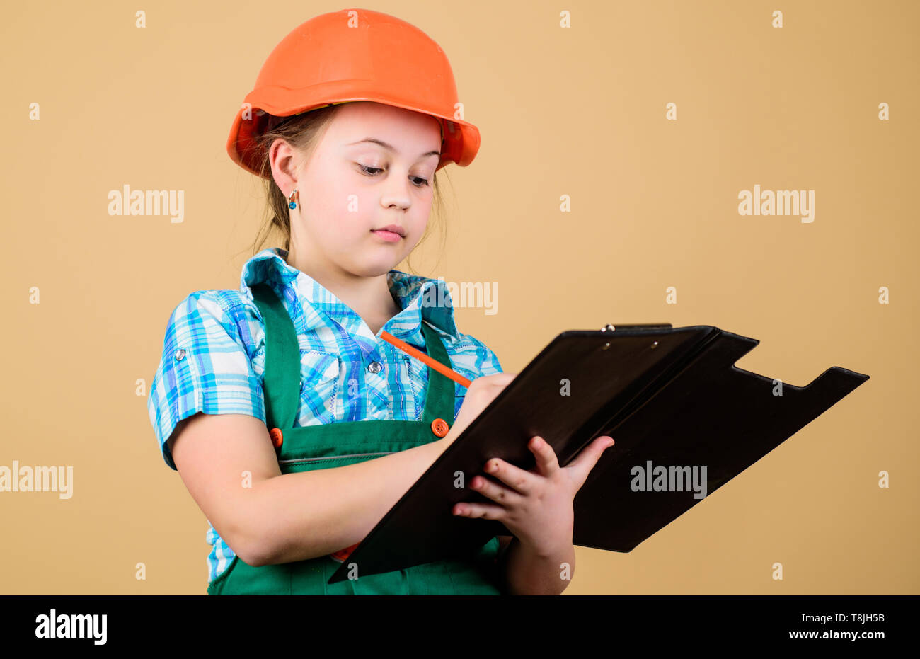 Future profession. Kid builder girl. Build your future yourself. Initiative child girl hard hat builder worker. Child care development. Safety expert. Foreman planning. Builder engineer architect. - Stock Image