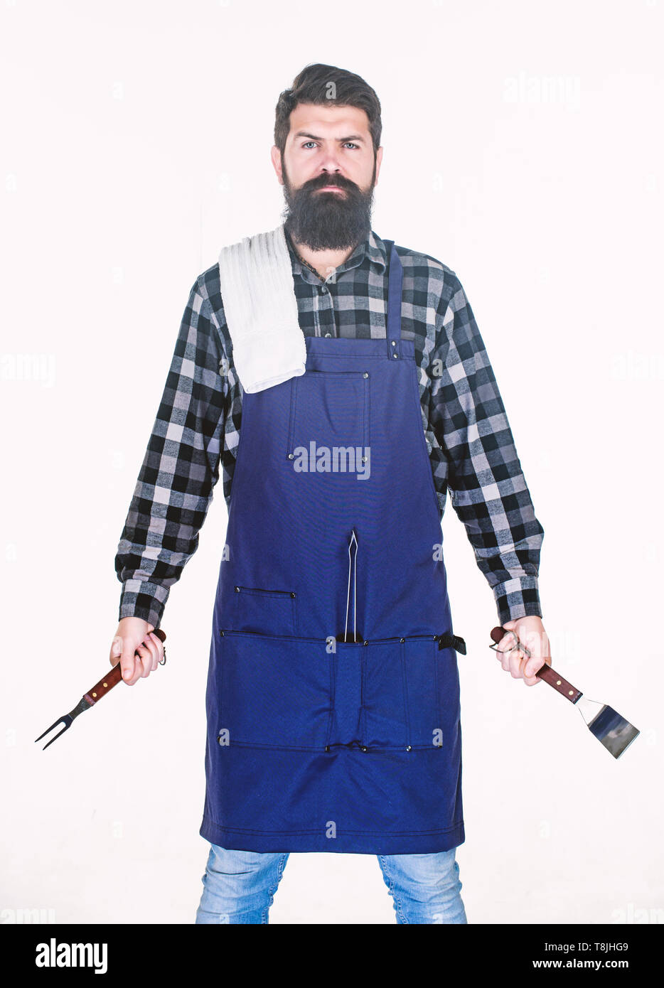 Man hold cooking utensils barbecue. Tools for roasting meat outdoors. Picnic and barbecue. Cooking meat in park. Masculine hobby. Bearded hipster wear apron for barbecue. Roasting and grilling food. - Stock Image