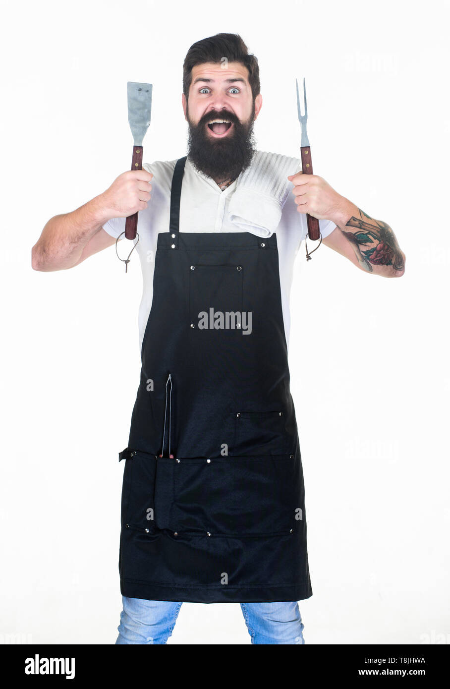 Kitchen utensils for keeping hands far away from heat. Grill cook with fork and spatula cooking utensils in hands. Bearded man holding barbecue utensils. Chef hipster with metal grill utensils. - Stock Image