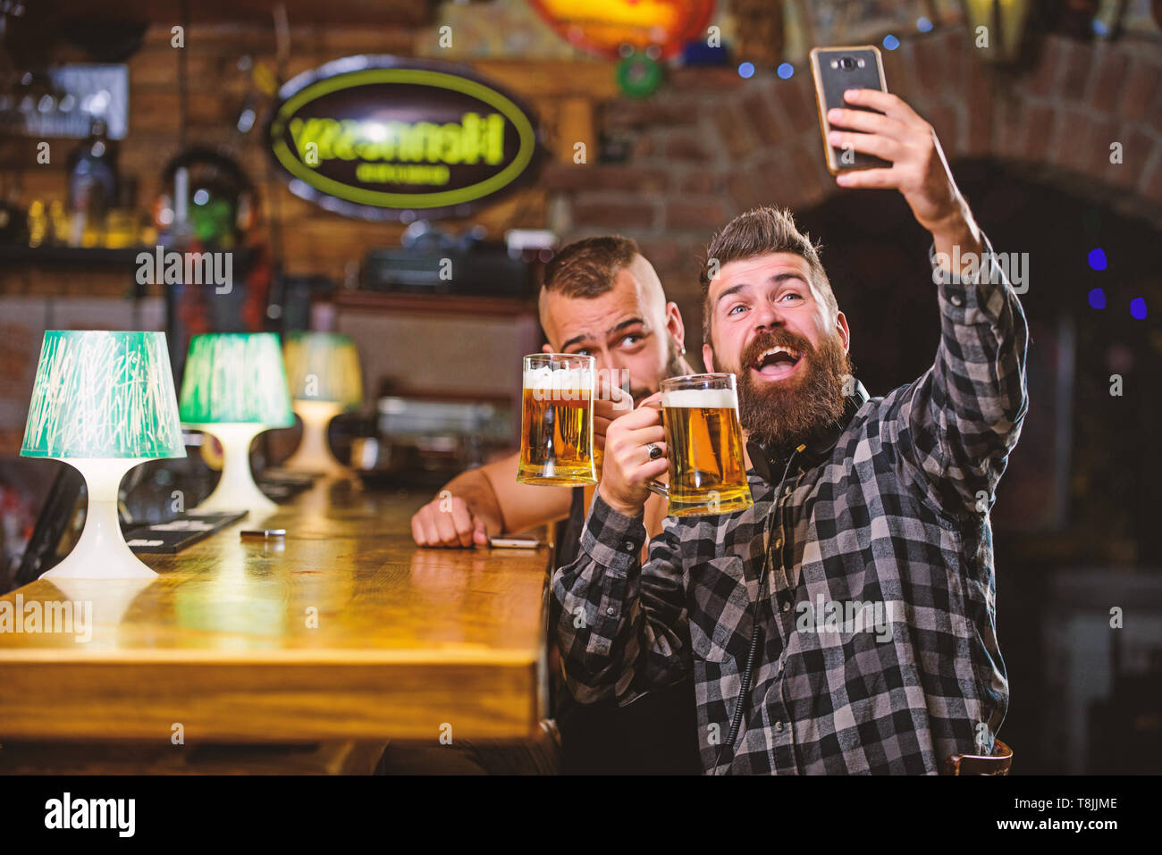 Send selfie to friends social networks. Man in bar drinking beer. Online communication. Man bearded hipster hold smartphone. Taking selfie concept. Take selfie photo to remember great evening in pub. - Stock Image