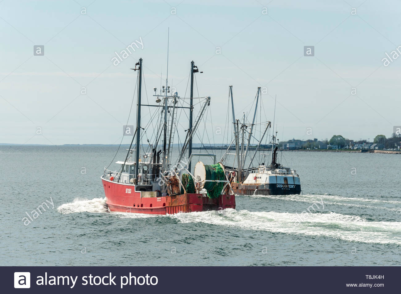New Bedford, Massachusetts, USA - May 8, 2019: Dragger Mary K easing past fishing vessel Discovery  crossing New Bedford outer harbor - Stock Image