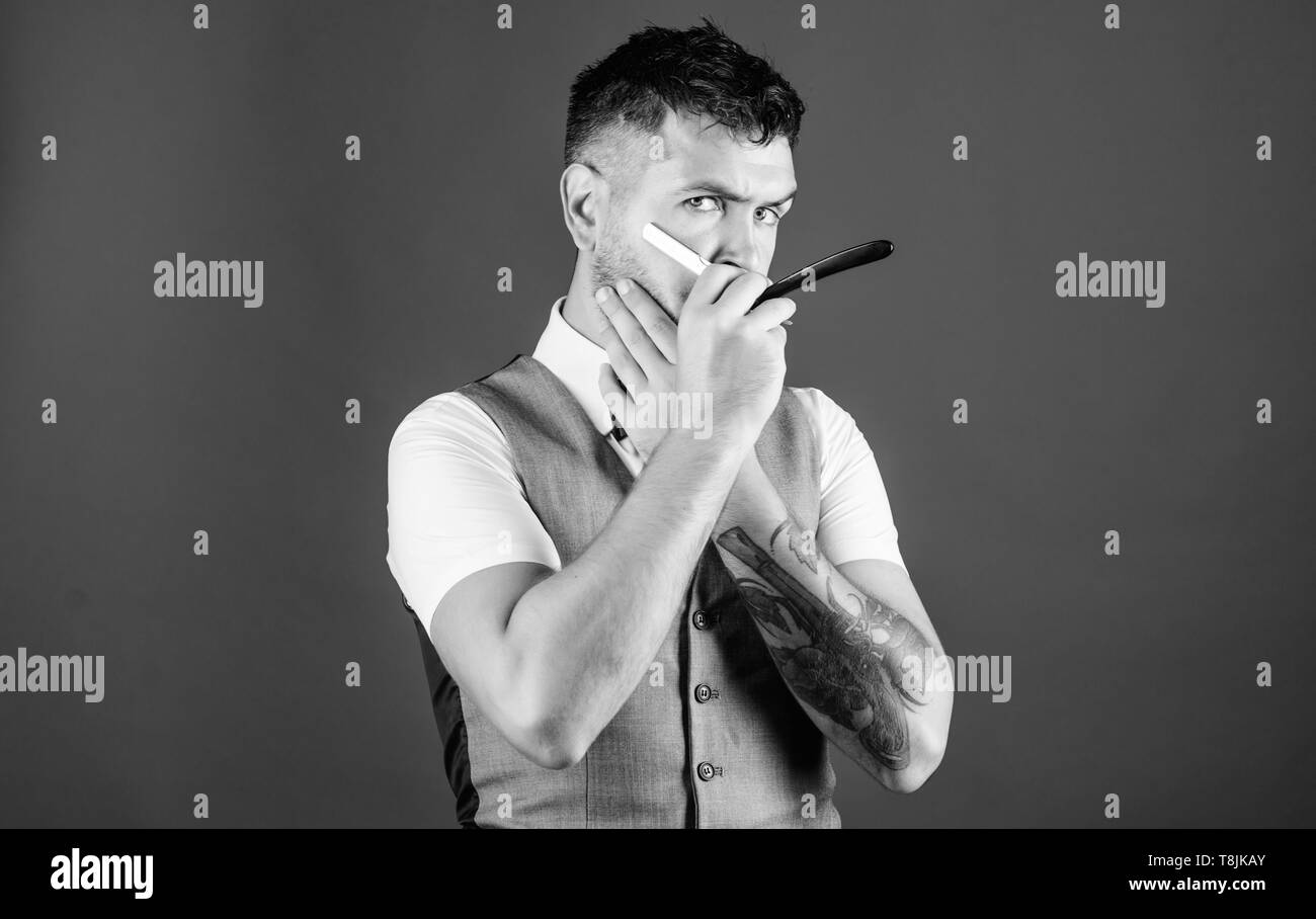 Razor barber shop. Bearded man with razor. Brutal man with beard holding shave razor. Hipster with retro razor for shaving beard. Barber with vintage barber tool. Bringing his beard to the next level. - Stock Image