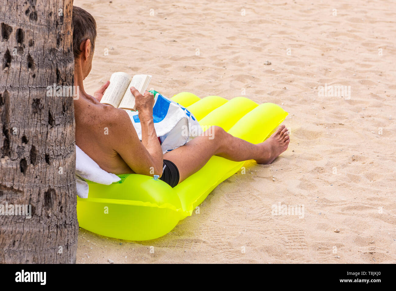 A man sitting off by himself reading a book on a yellow floatation device, Waikiki Beach, Hawaii, USA. Stock Photo
