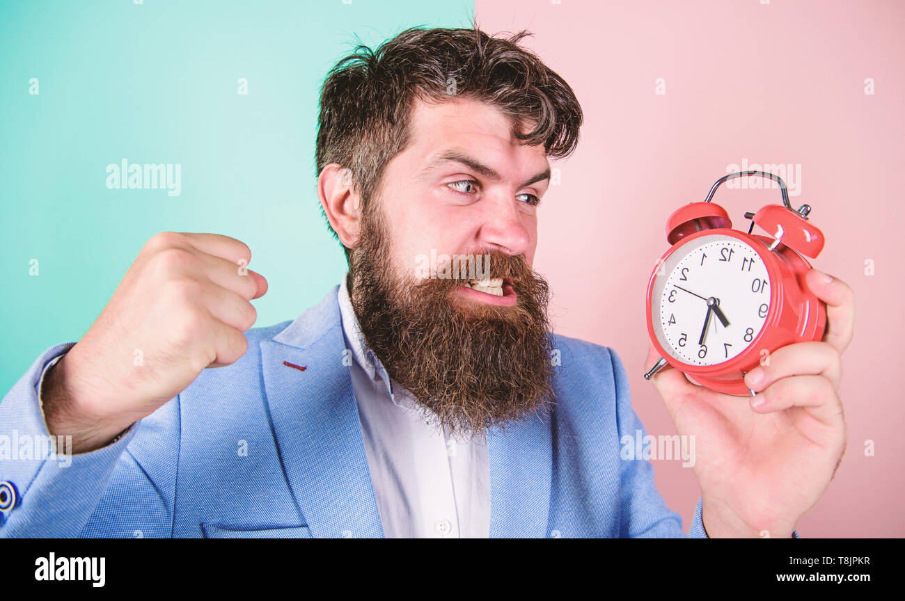 Man bearded aggressive businessman hold clock. Stress concept. Hipster stressful working schedule. Businessman has lack of time. Time management skills. How much time till deadline. Time to work. - Stock Image
