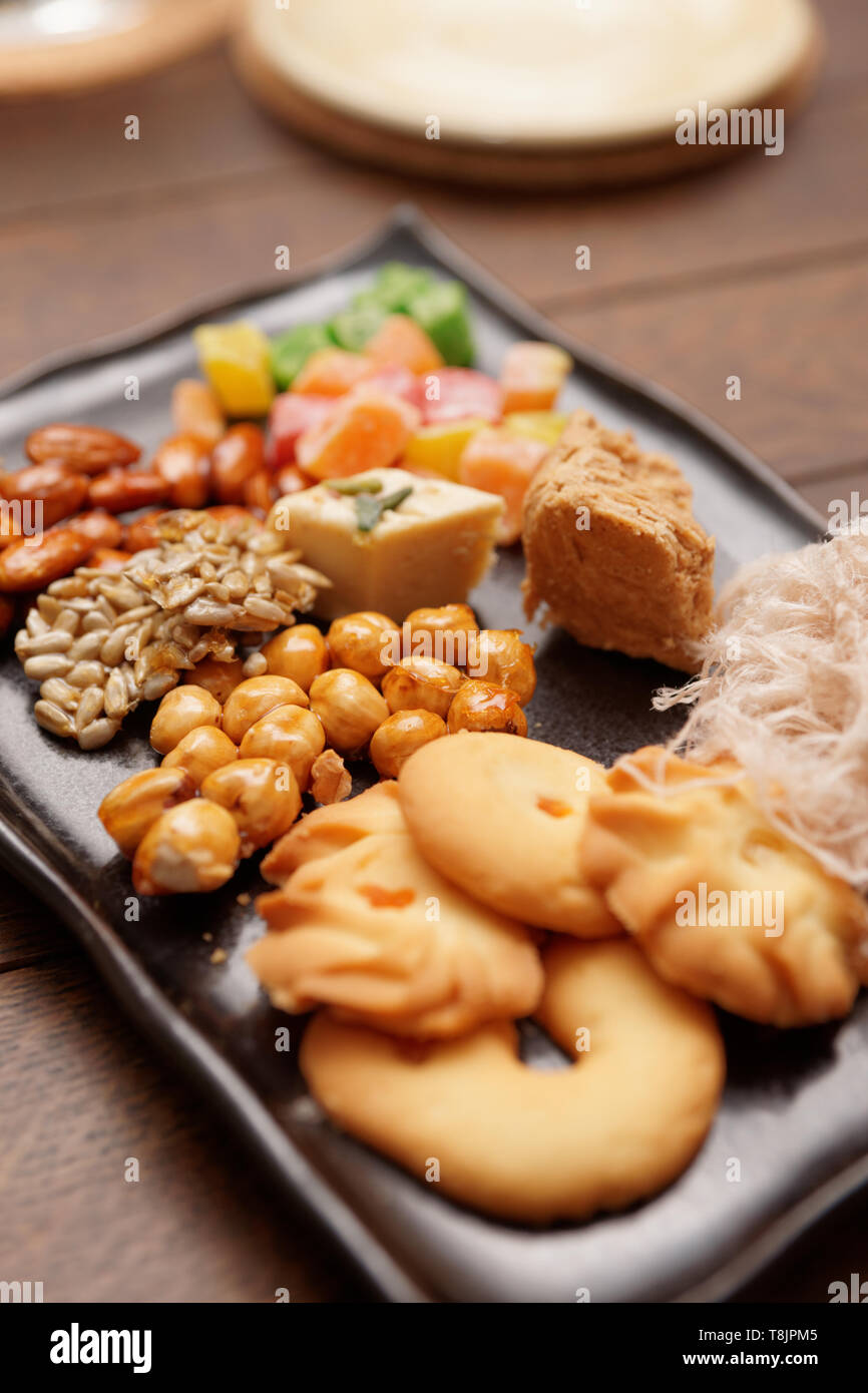 Oriental sweets on plate on wooden table - Stock Image