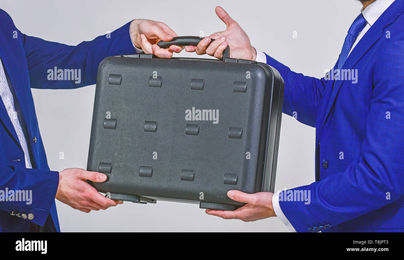 Business transfer concept. Male hand hold briefcase. Handover of case in hands of business partners. Handover of illegal goods. Illegal deal handover. Hands give briefcase for exchange or offer bribe. - Stock Image