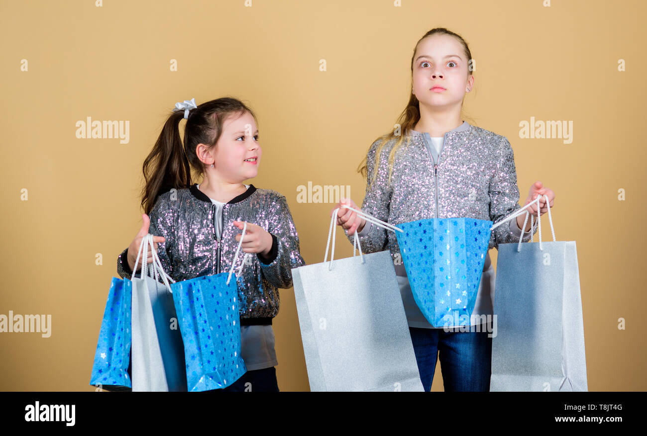 Shopping and purchase. Black friday. Sale and discount. Shopping day. Children hold bunch packages. Kids fashion. Expect more. Pay less. Girls sisters friends with shopping bags beige background. - Stock Image