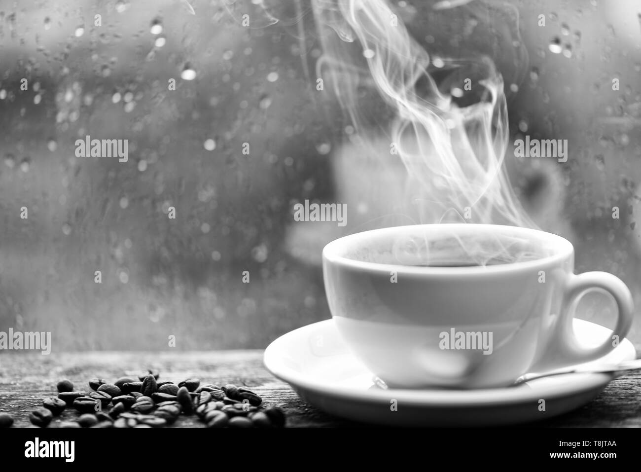 Wet glass window and cup of hot coffee. Autumn cloudy weather better with caffeine drink. Enjoying coffee on rainy day. Coffee morning ritual. Fresh brewed coffee white mug and beans on windowsill. - Stock Image