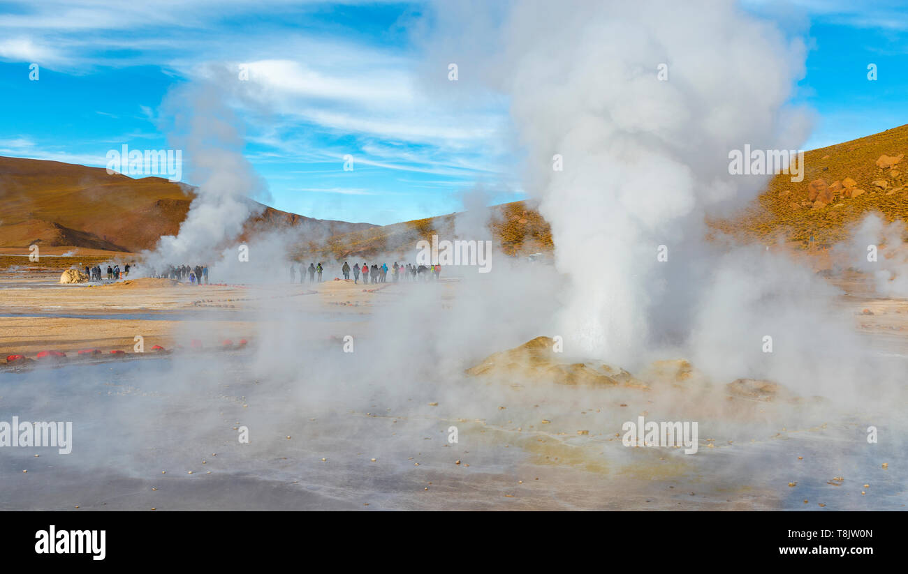 A large group of unrecognizable tourists in the vapor trails, fumaroles and geyser cones of the Tatio Geyser field at sunrise, Atacama Desert, Chile. - Stock Image