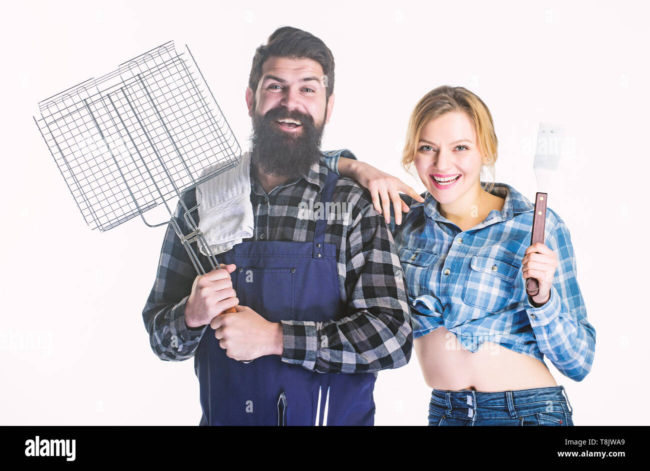 Tools for roasting meat. Couple in love hold kitchen utensils. Family weekend. Man bearded hipster and girl. Preparation and culinary. Picnic barbecue. food cooking recipe. Love is in the air - Stock Image