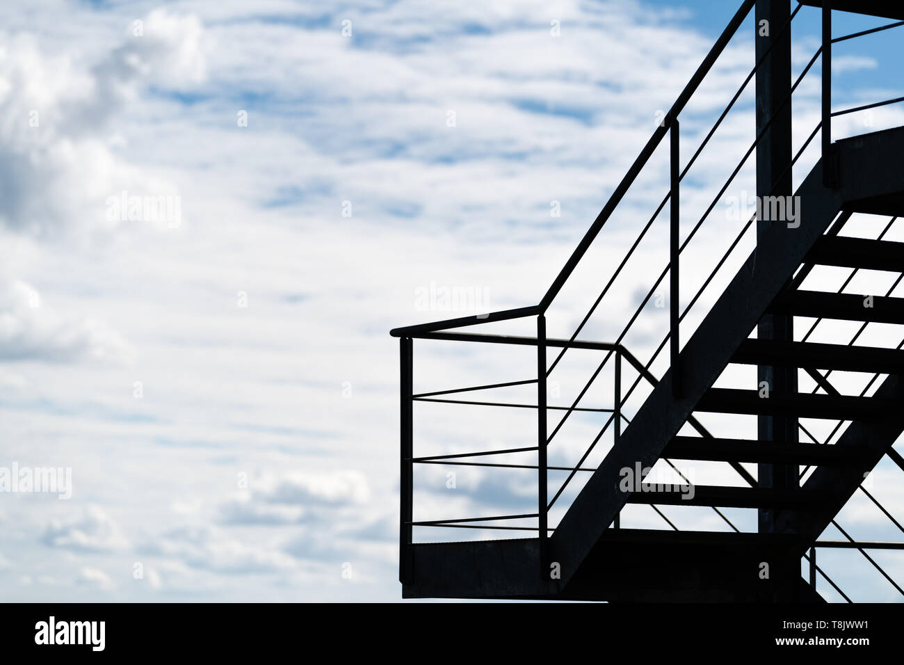 Stairway to heaven - a fire escape or an external staircase on a building silhouetted against a cloudy sky Stock Photo