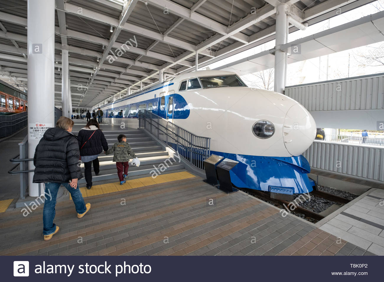 Visitor walking past the 0 Series Shinkansen on display in the 100 ...