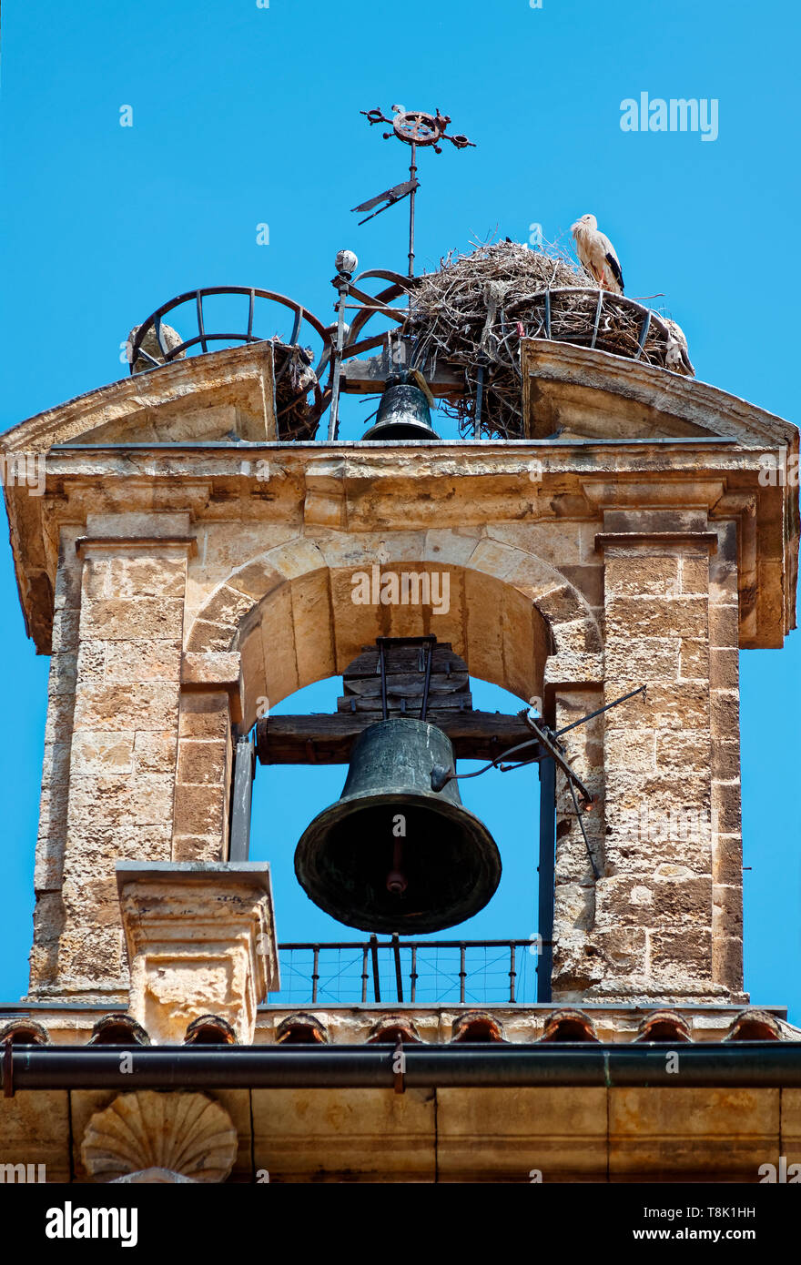 bells, old stone tower; 2 birds' nests, wildlife, weathervane, UNESCO site; Europe; Salamanca; Spain; spring, vertical - Stock Image